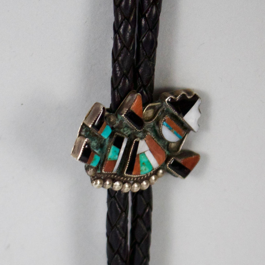 One of a kind. This handsome bolo features an intricate Zuni design with detailed stone inlay. The Zuni design is of a dancing man.