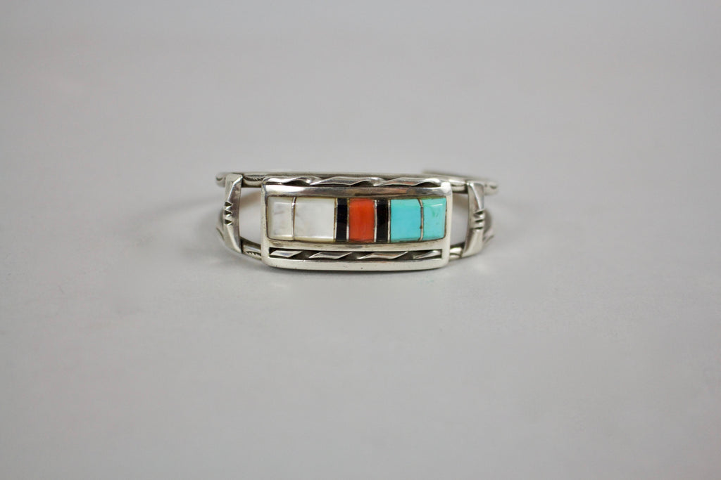 This beautiful bracelet features various turquoise, Mother of Pearl, onyx, and coral, crafted together to make an intricate design. This bracelet is an estate jewelry cuff.