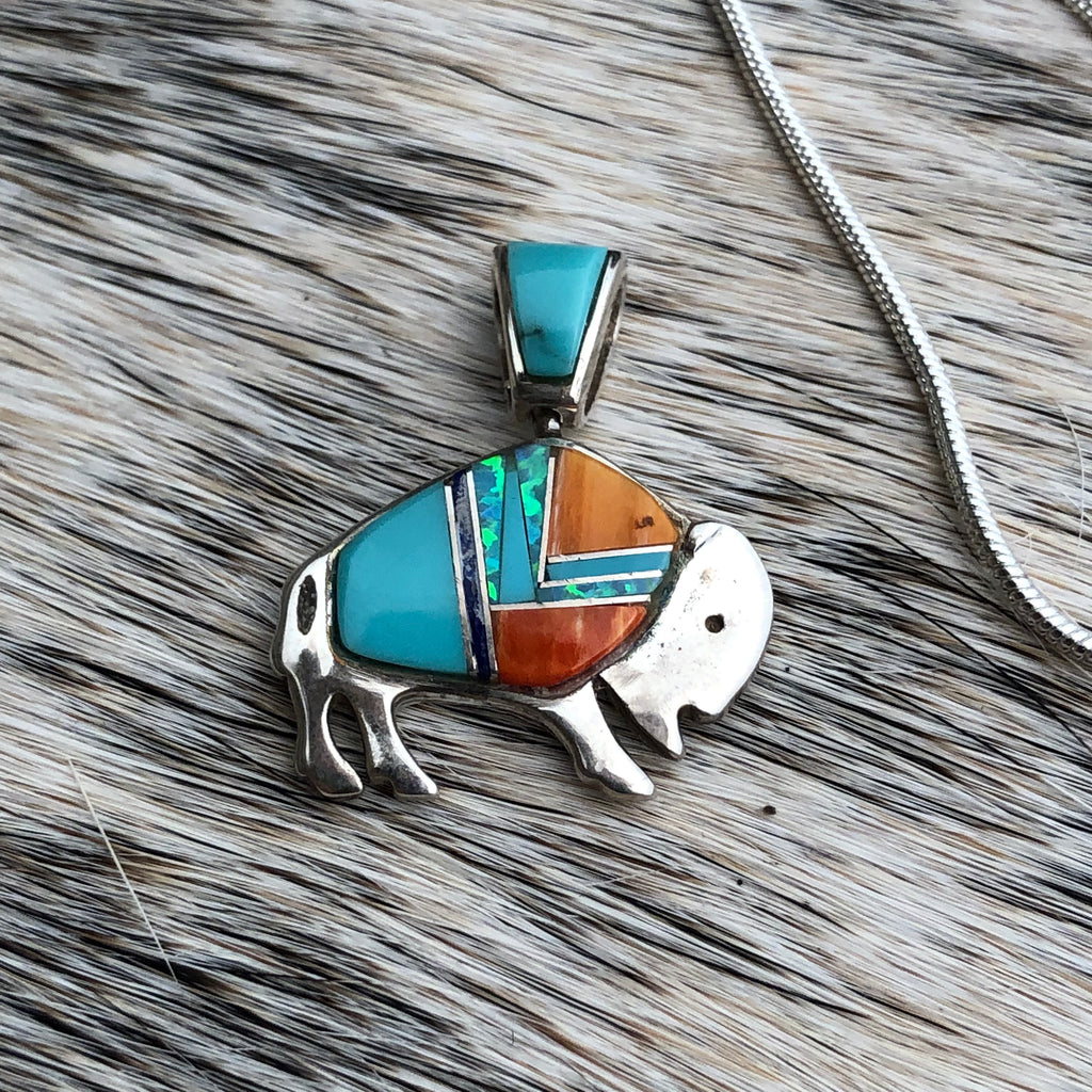 This beautiful bison pendant necklace features various inlayed stones including turquoise. Bison is recognized as a symbol of strength.