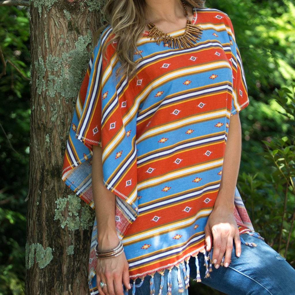 This Ryan Michael serape striped poncho features hand knotted fringe and a vibrant Southwestern fashion design. T1611NS