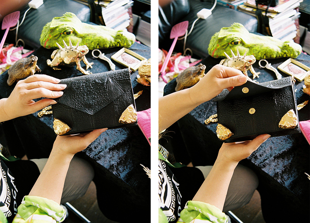 a cane toad leather handbag in black with gold metal corners