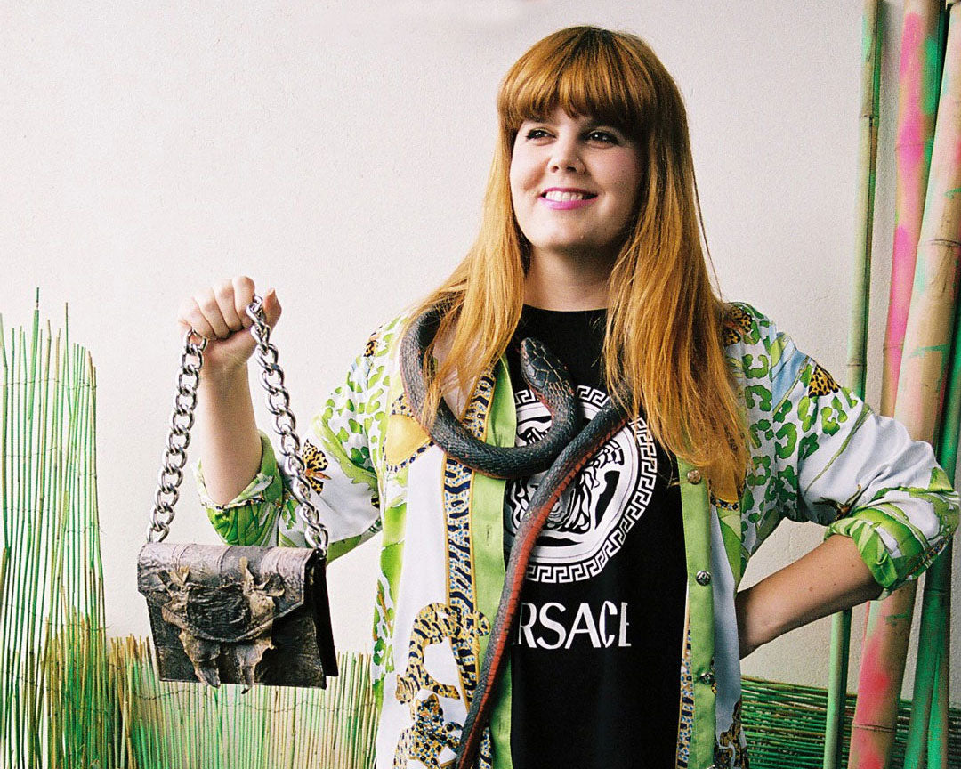 Lia Tabrah, a woman stands holding a luxury handbag made from toad leather and chunky chrome chain. she is wearing a rubber snake around her neck, and is surrounded by an artificial green landscape.