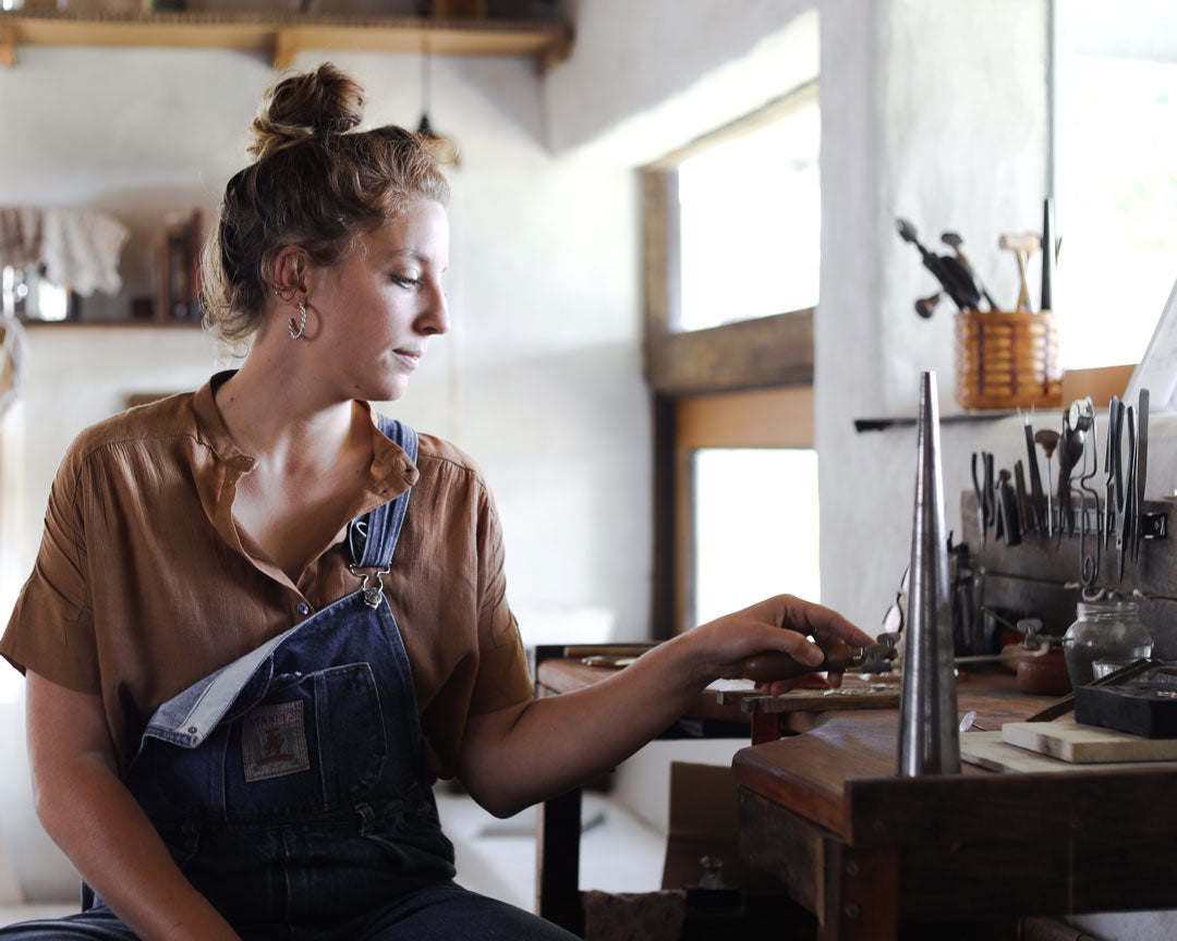 Elizabeth Herman in her denim overalls, sitting at her jewellery workbench