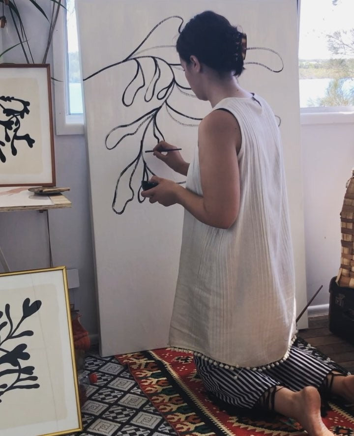 Delta Venus painting a black line drawing on a white canvas