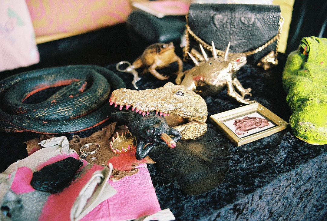 ornaments found inside Lia Tabrah's creative studio. a gold crocodile head figure has captured a black cane toad smoking a cigarette.