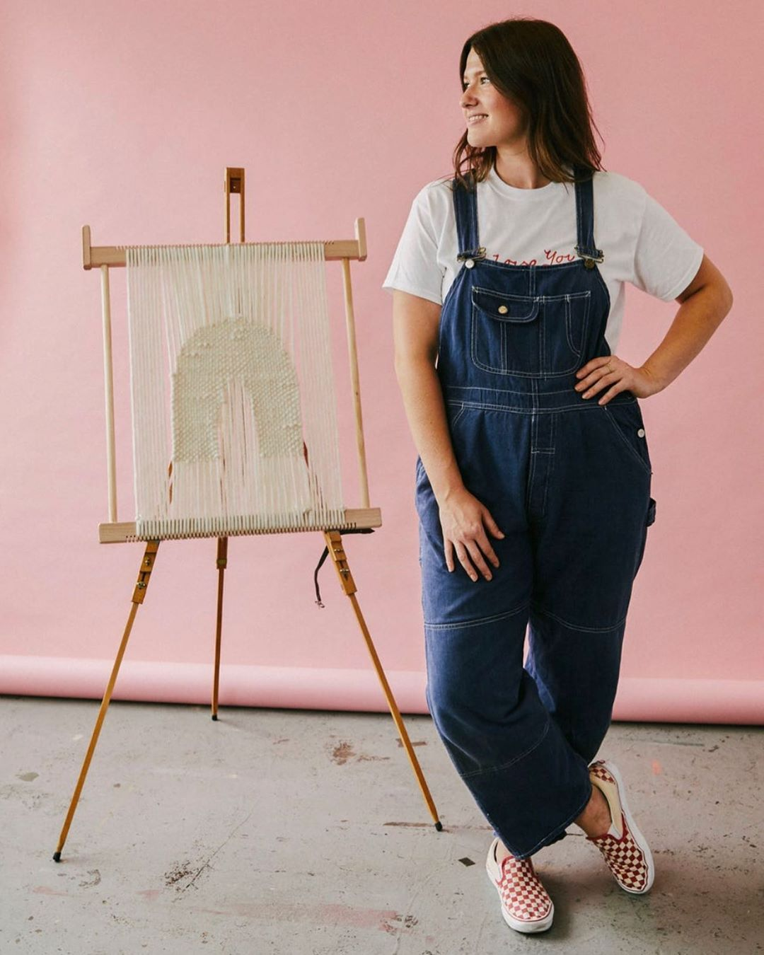 Rachel Wood wearing denim overalls and a white t-shirt posed next to her woven artwork