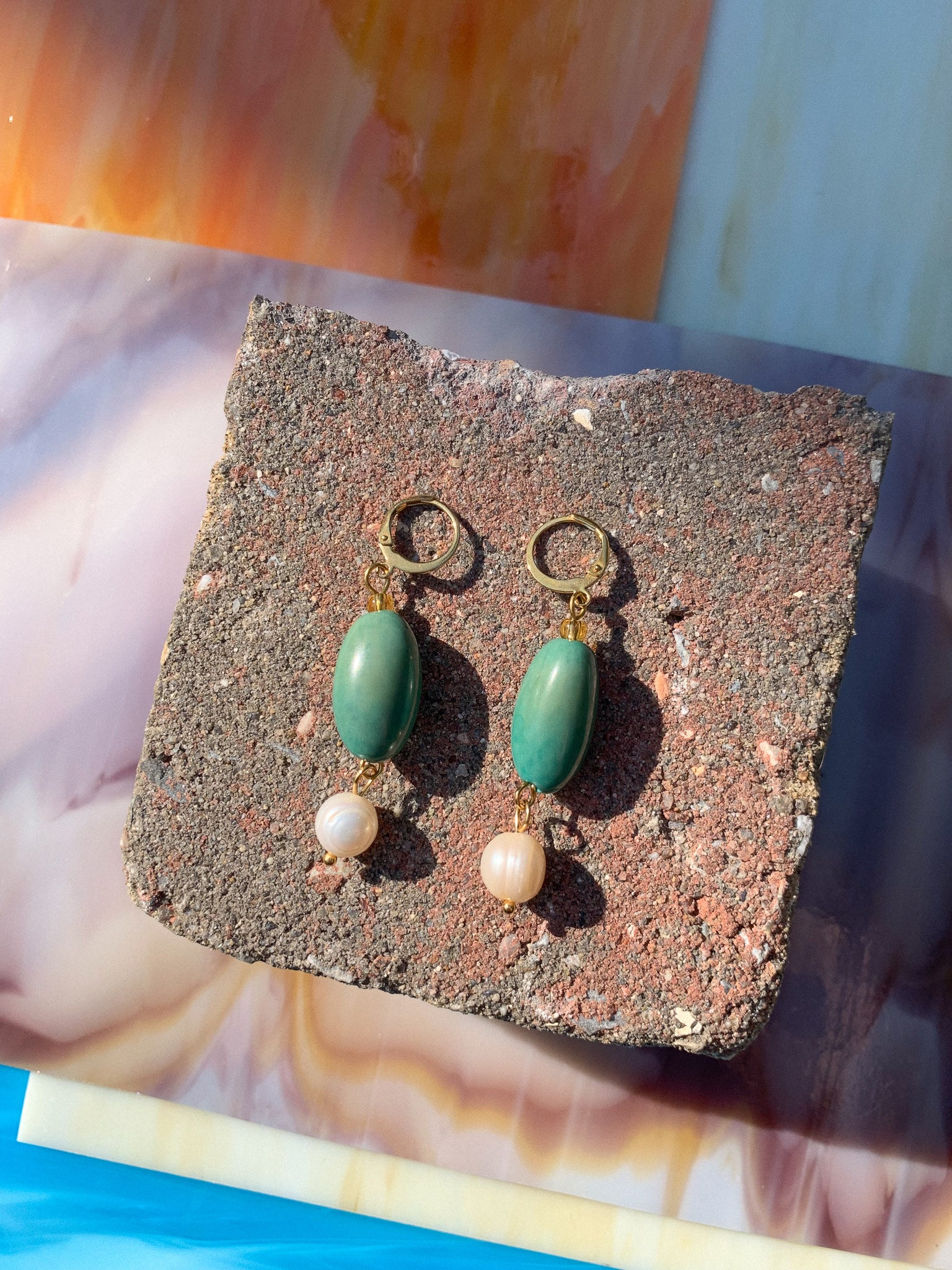 Handmade earrings featuring aqua vísola seeds