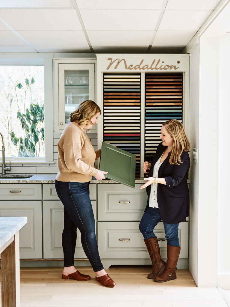 Kristina Crestin and Leah Bonarrigo picking samples from Medallion Cabinetry
