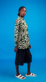 model wearing a green flower print shirt with a blue background