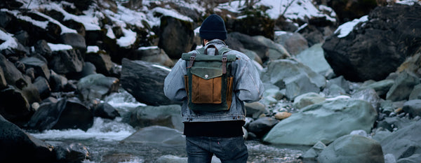 a guy with his vintage backpack traveling near a river