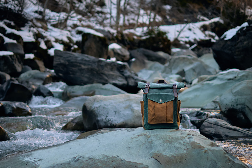 Lund canvas roll top backpack on a river bed