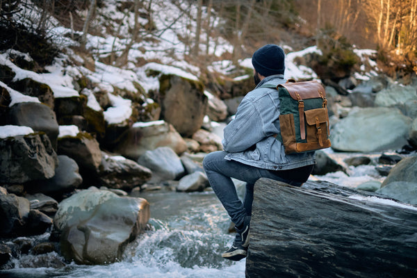 guy sitting a rock wearing a canvas backpack