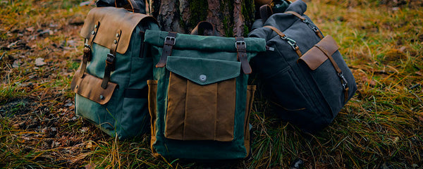 three vintage leather and canvas backpack named helsinki lund and reykjavik laying against a tree