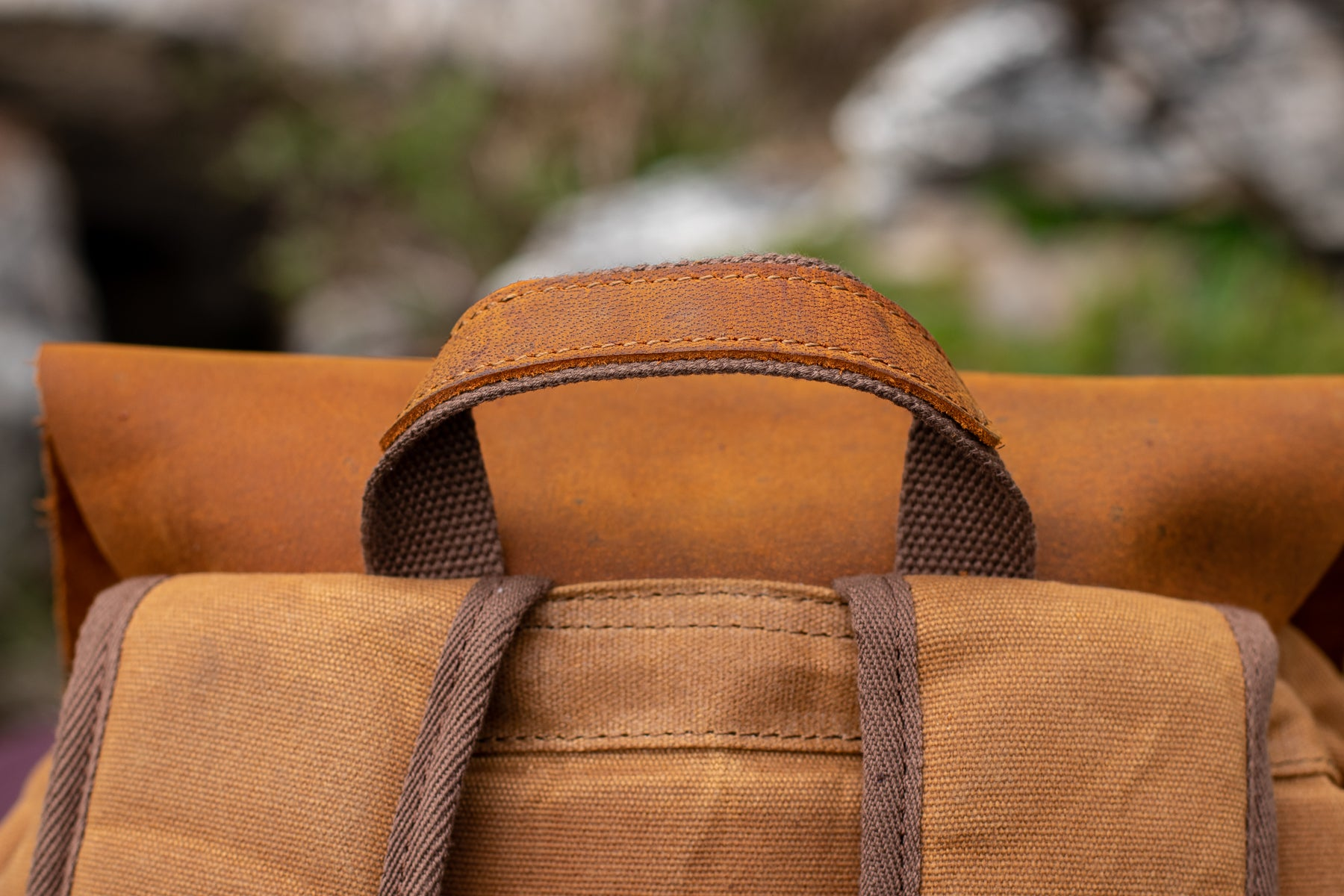 close up view of the leather cap and the top leather handle of the waxed bag