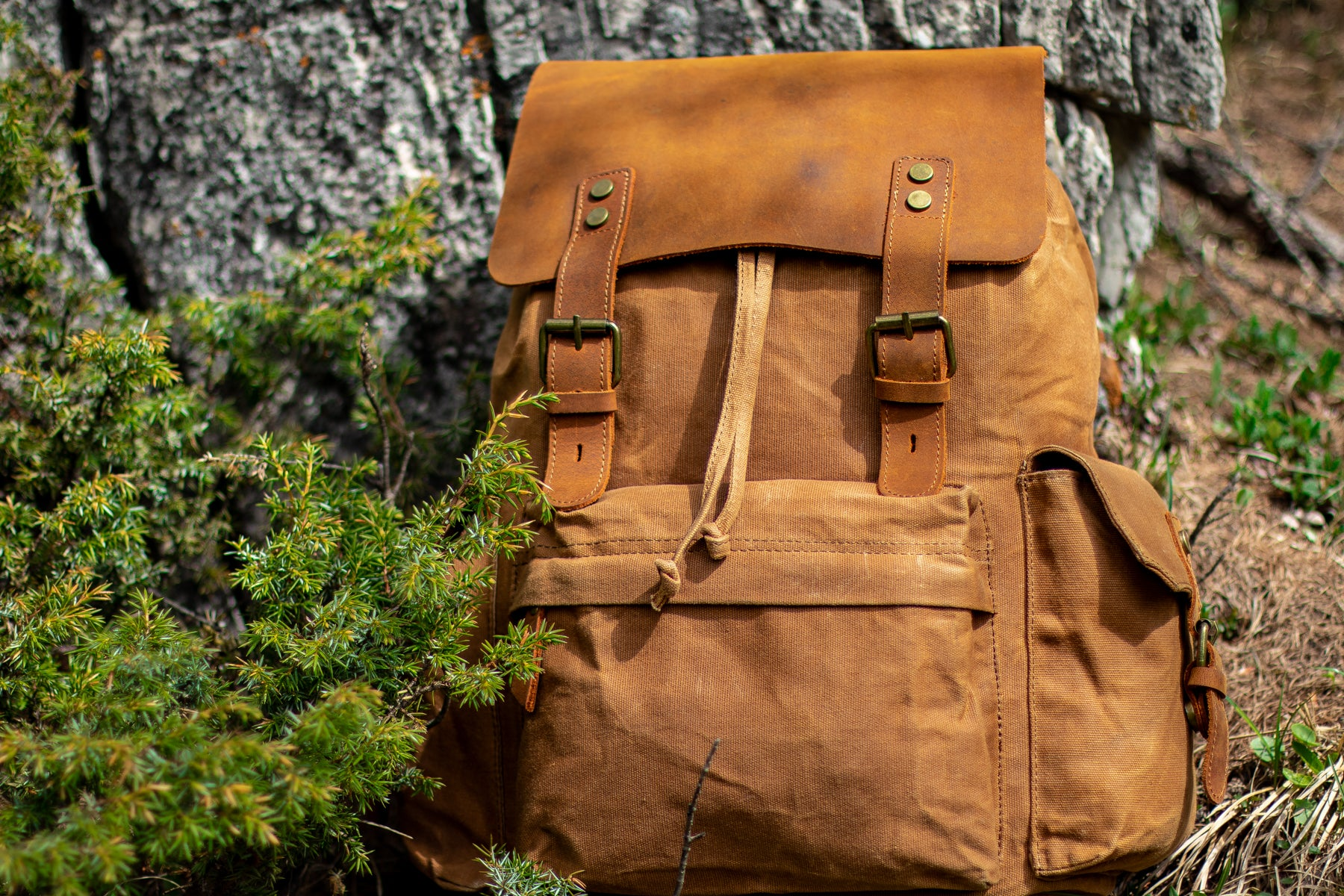 travel waxed canvas and leather backpack for men and women laying on a rock