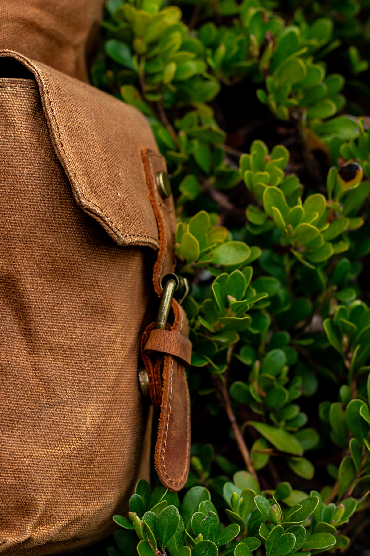 large and roomy exterior side flap pockets of the waxed canvas backpack