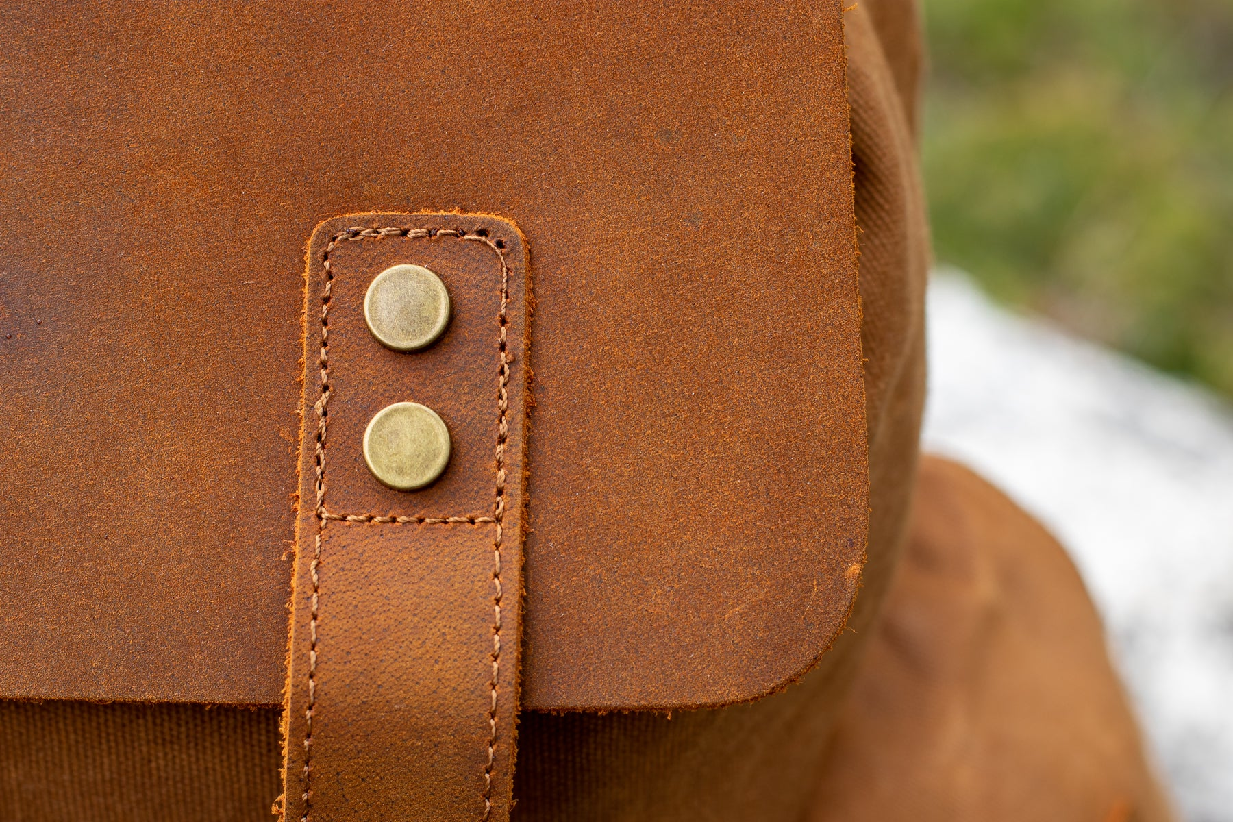 close up view of the gold tone protective rivet on the leather cap of the waxed canvas backpack