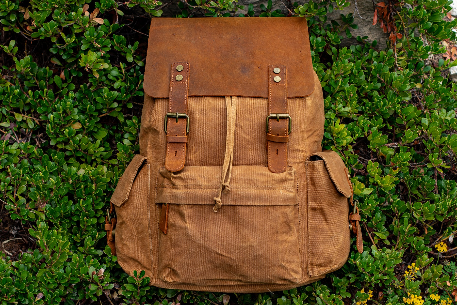 A waxed canvas backpack in khaki colors sitting on a field of wild grass