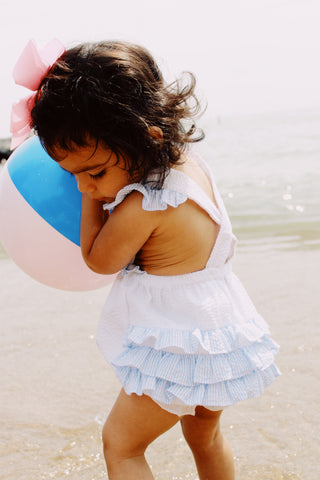little girl at beach with beachball and ruffle playsuit