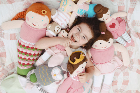 little girl smiling covered in knit Zubel toys