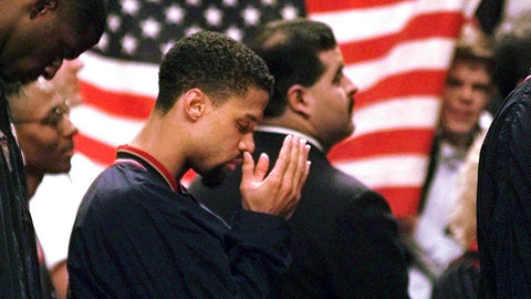 Mahmoud Abdul-Rauf with his hands in prayer during the national anthem