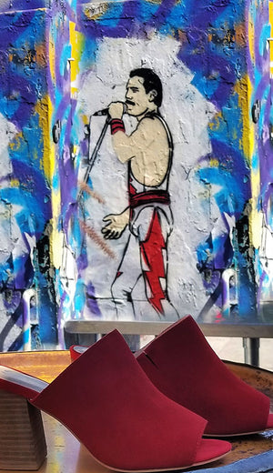 A tall narrow banner featuring a pair of red peeptoe mules with block stacked leather heels sitting on a table in the foreground, with a spraypainted psychedelic mural of Freddie Mercury in the background.