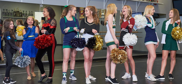Group of female cheerleaders standing around holding their poms with a Pom Pony