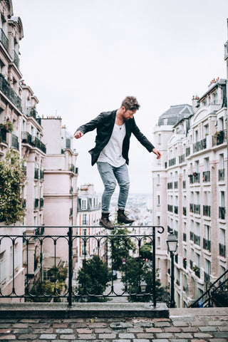 Fashion confident male balancing on a rail above the city