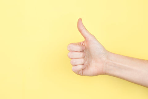 A hand giving the thumbs up sign indicating good products and customer service at TwiLd Capit Hog