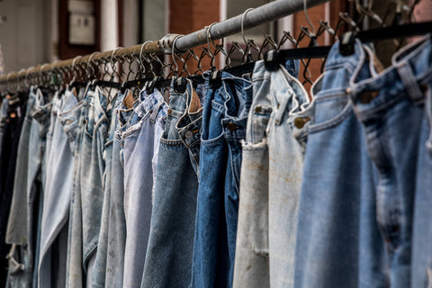 Various washes of vintage denim jeans hanging on a rail are upcycled at TwiLd Capit Hog