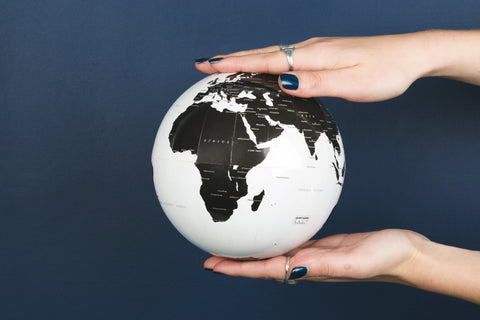 Hands holding a globe represents TwiLd Capit Hog accessories going global. Photo by Sarah Pflug from Burst