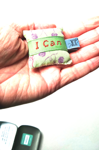 Tiny empowerment pillow shown in the palm of the hand