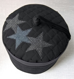 The uniquely quilted and beaded tip of the smoking cap with applique stars