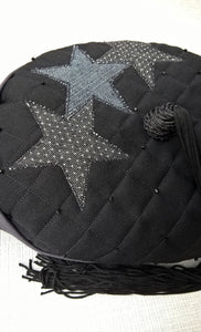 The tip of the smoking cap has three applique stars in two different denims
