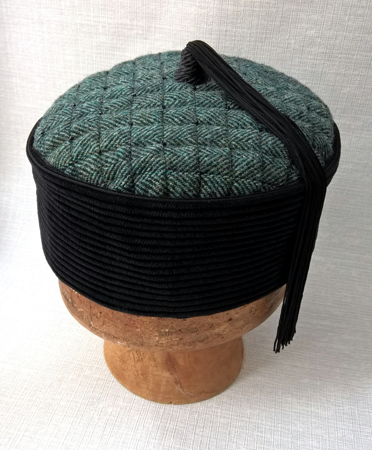Oriental style tassel smoking cap with a green herringbone tip and black corduroy crown