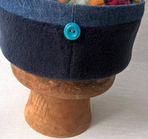 A simple turquoise button at the back finishes this handmade winter fleece and denim fez