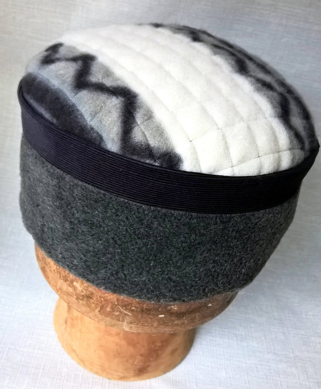A handmade fleece winter ethnic hat in grey off white and navy