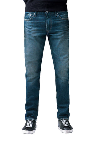 S.M.N Studio's Hunter in Sundance Men's Jeans. A slim fit darker blue wash jean accented with contrasting fades and whiskers for a worn in look. It's made in a comfort stretch Japanese denim.