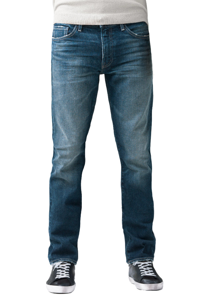 S.M.N Studio's Bond in Sundance Men's Jeans. A slim straight darker blue wash jean accented with contrasting fades and whiskers for a worn in look. It's made in a comfort stretch Japanese denim.