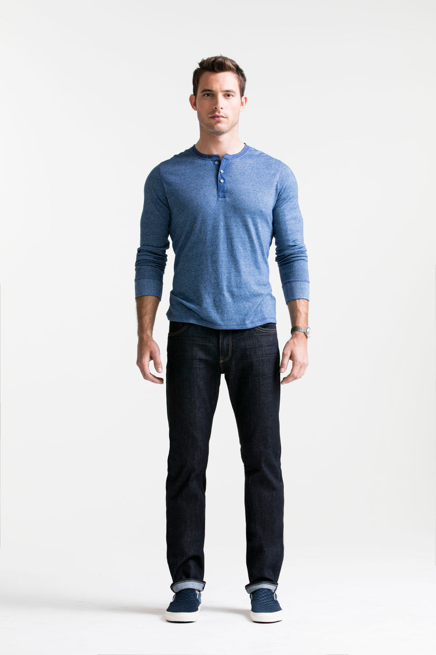 Brown haired athletic model standing in SMN Studio's Bond in Bravo Men's Jeans and blue henley. The jeans are a slim straight raw denim washed jean.