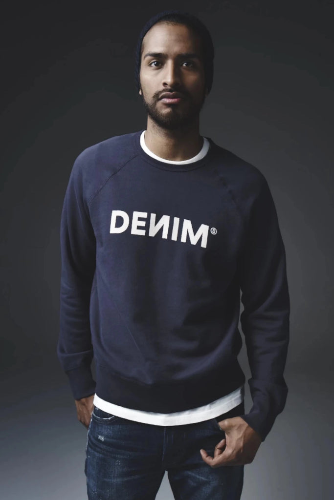 Model wearing S.M.N Studios DEИIM College themed Navy Sweatshirt