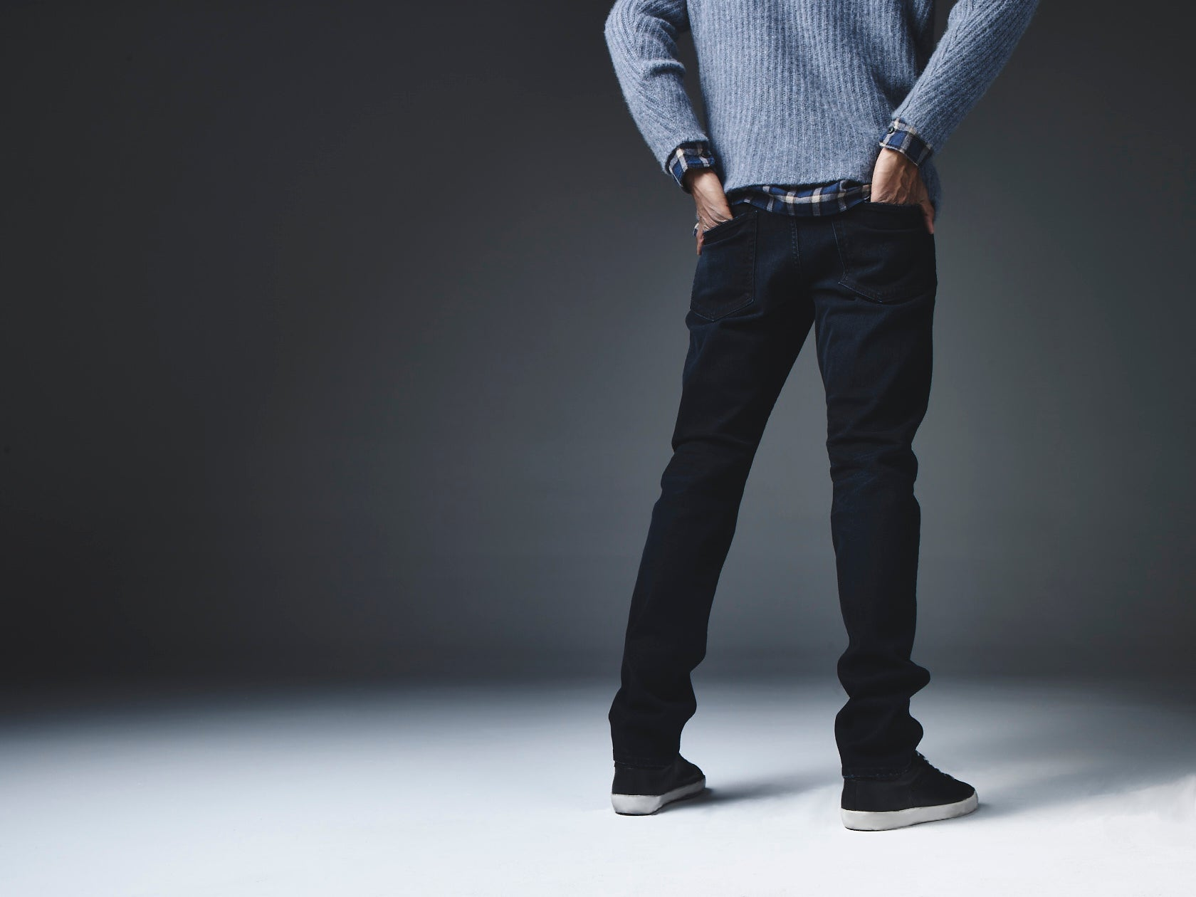Back shot from shoulder down of a model standing with his hands in his back pocket against a dark background wearing a grey sweater and S.M.N Studio Bond in Shadow jeans.