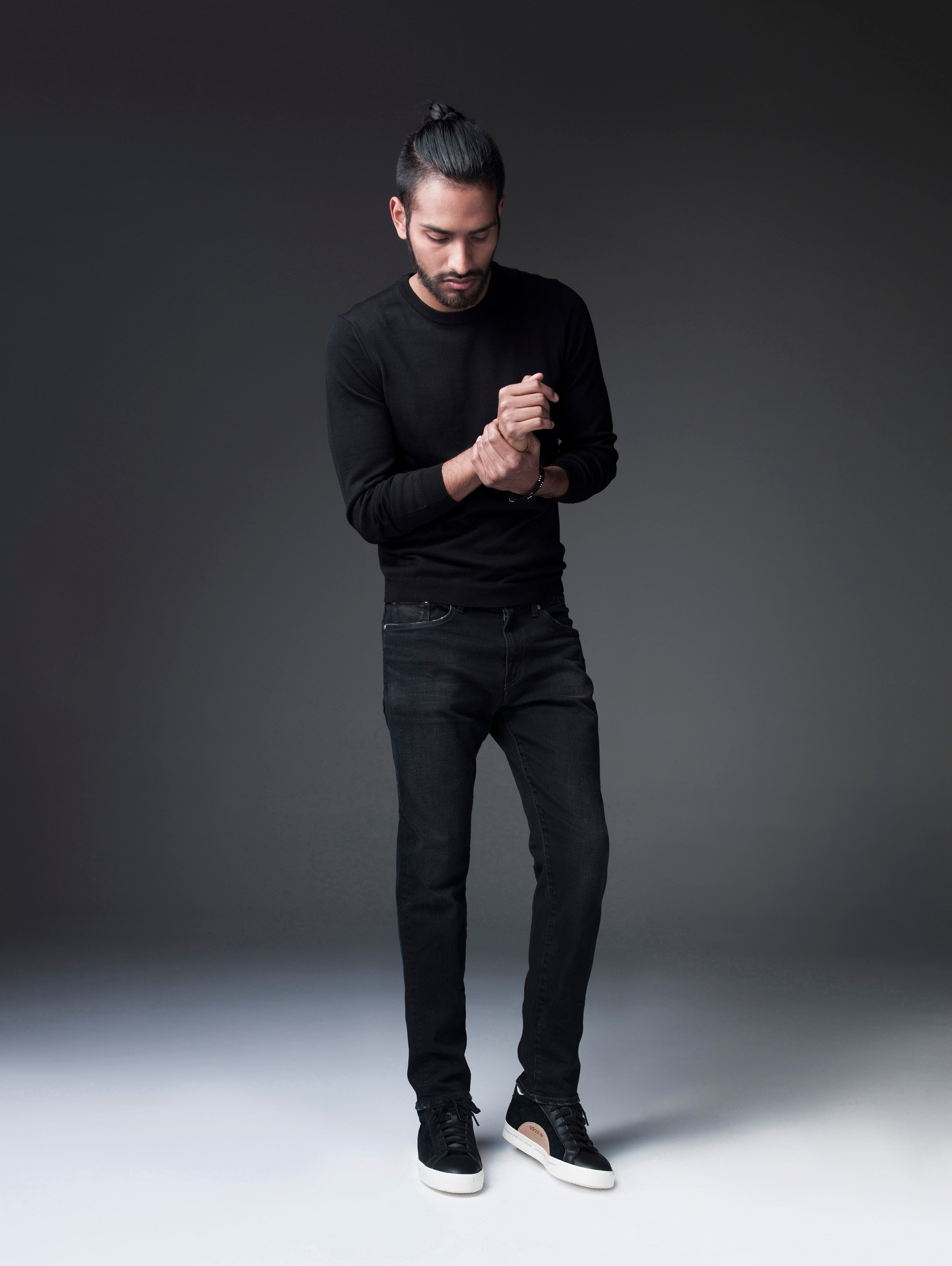 Ponytailed model dressed in all black with a black sweatshirt, S.M.N Studio's Finn in Black Rock, and black tennis shoes. He's in front of a heavily shadowed background grabbing his right wrist with his left hand.