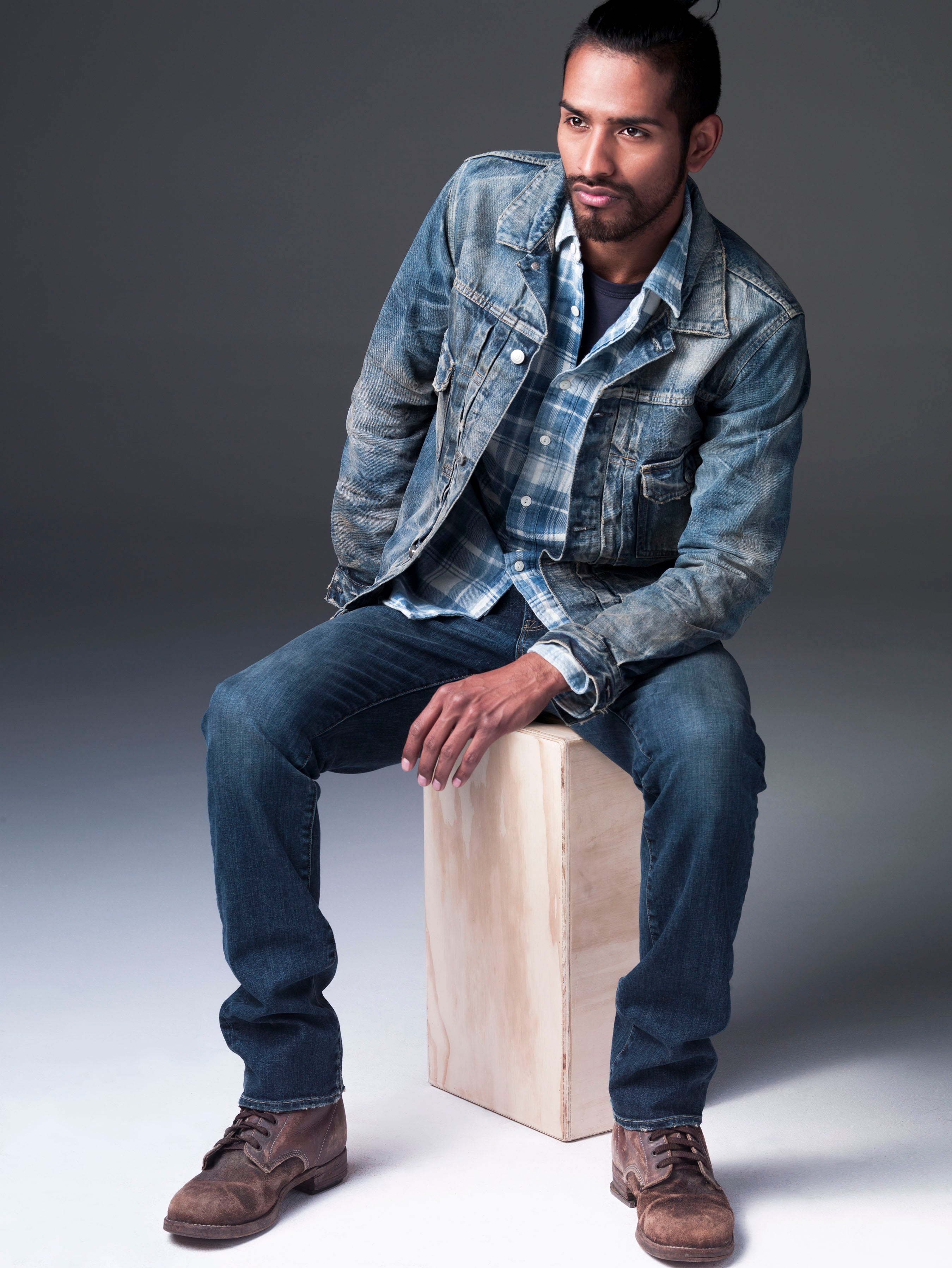 Ponytailed and bearded dark skinned model sitting on wooden box while leaning over to his left side. He is wearing S.M.N Studio's Trucker Jacket in Morrison with a plaid shirt underneath, Bond in Odyssey slim straight jeans, and dark brown boots.