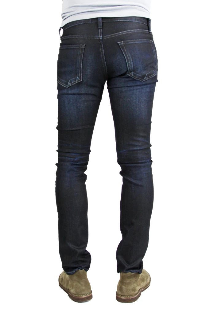 Back of S.M.N Studio's Hunter in Empire Men's Jeans - Slim fit jeans made up in a premium comfort stretch denim with a dark indigo wash characterized by light contrast fades, accented 3D whiskers, and honeycombs