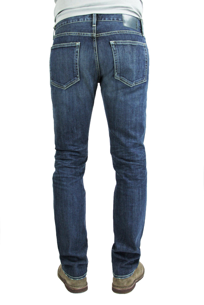 Back of S.M.N Studio's Hunter in Odyssey Men's Jeans - Slim fit medium vintage indigo washed denim contrasted by light fading throughout the jeans including whiskers and honeycombs