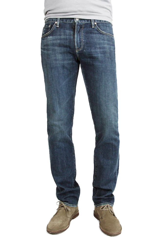 S.M.N Studio's Hunter in Odyssey Men's Jeans - Slim fit medium vintage indigo washed denim contrasted by light fading throughout the jeans including whiskers and honeycombs