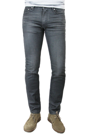 S.M.N Studio's Finn in Graphite Men's Jeans. A tapered slim fit fresco effect local coated dark charcoal washed jean. It's in a comfort stretch premium Japanese denim with slight contrast fades and 3D whiskering.