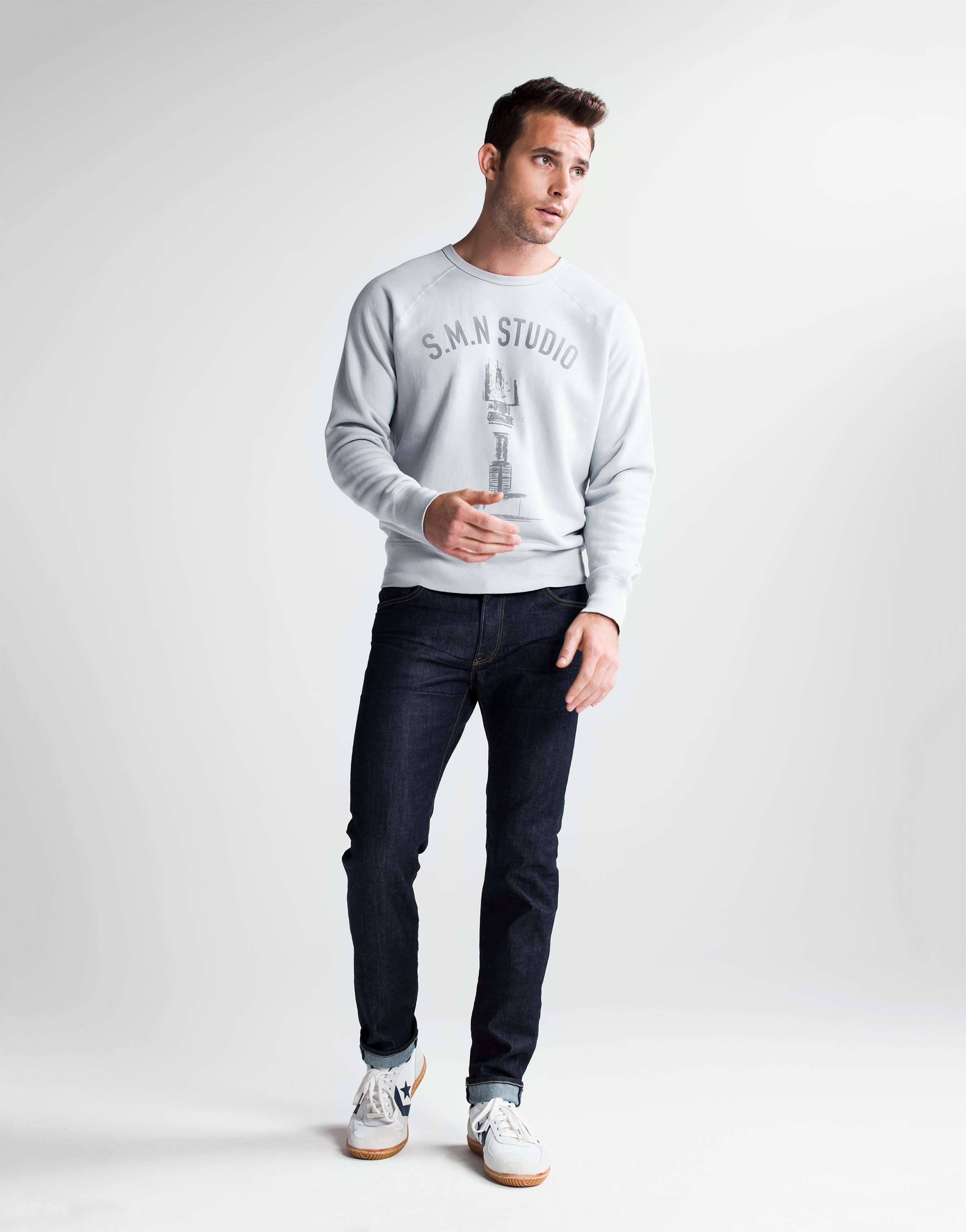 Brown haired athletic model standing wearing SMN Studio's Bond in Bravo jeans and S.M.N Studio printed grey crewneck sweatshirt. The jeans are a slim straight raw denim washed jean.