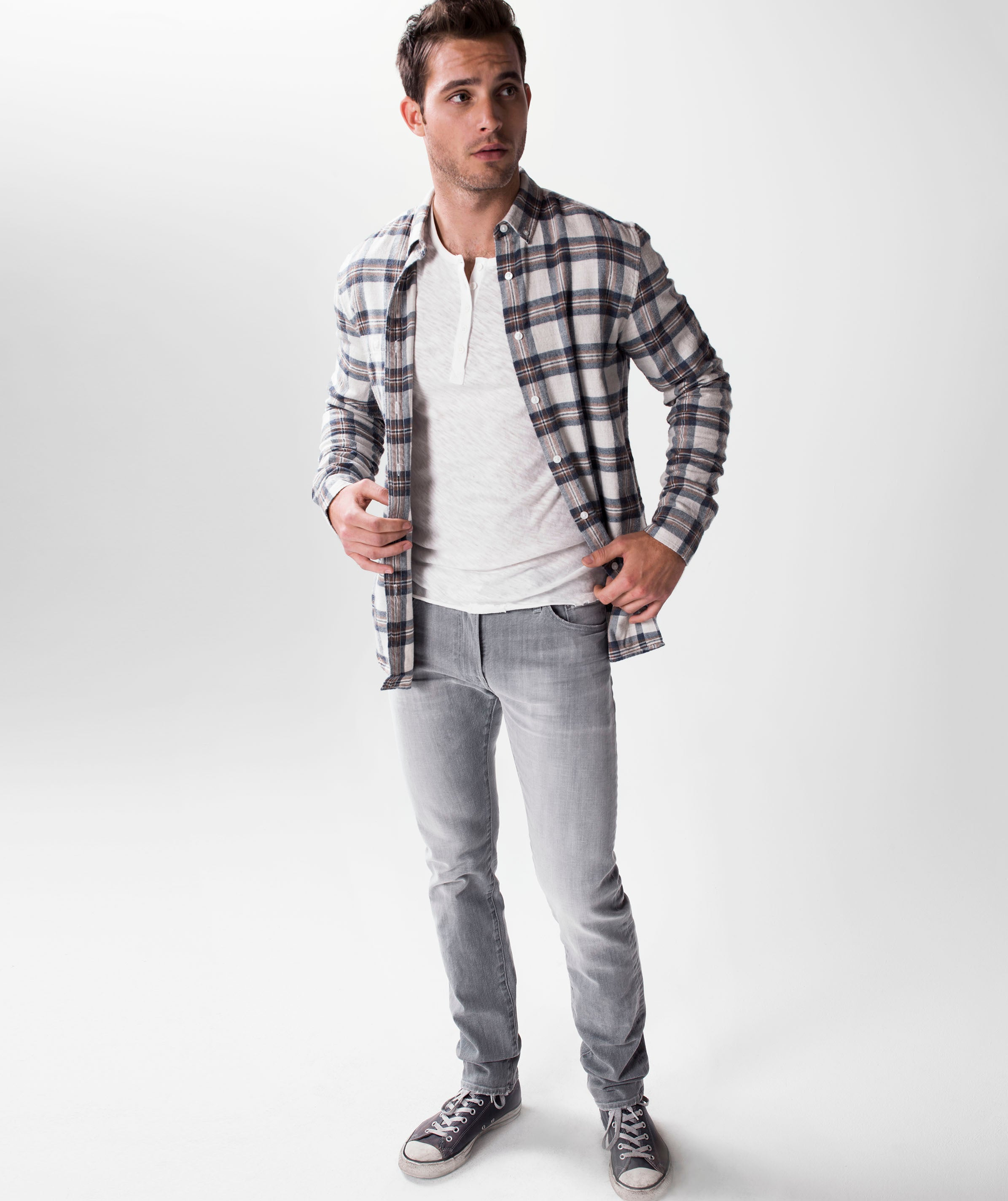 Model wearing S.M.N Studio's Hunter in Owen Men's Jeans with a casual outfit completed by a flannel and henley shirt underneath